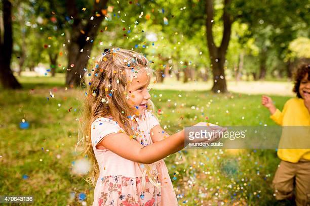 Glückliches kleines Mädchen, die Spaß mit bunten Konfetti im park