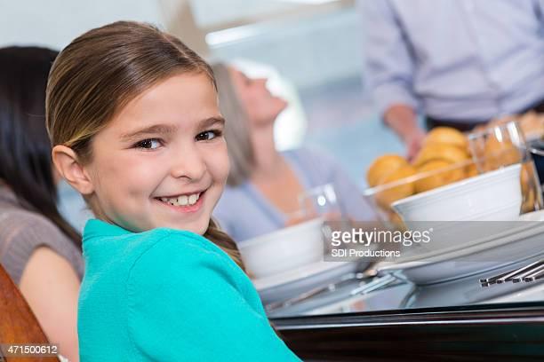 Fillette heureus'avoir repas en famille à table