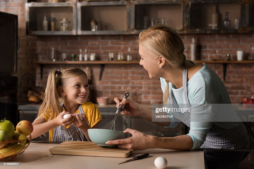 Happy little girl helping her mother in the kitchen : Stock Photo