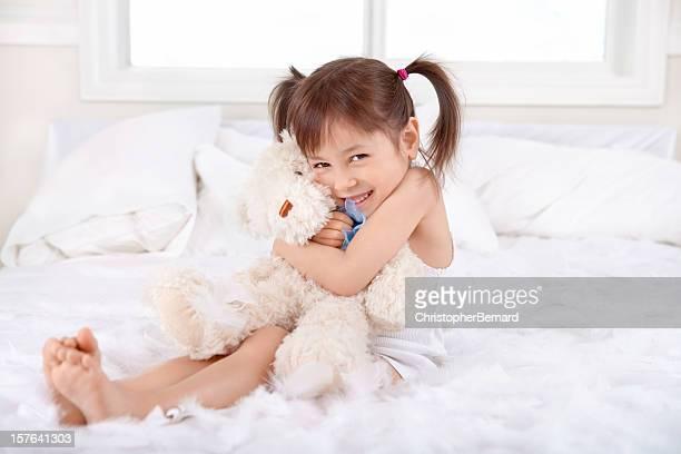 Bambina felice abbracciare orsacchiotto a letto