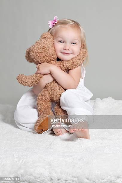 Happy Little Girl in White Dress Hugging Stuffed Animal