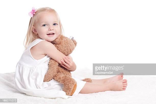 Heureuse petite fille en robe blanche se tenant peluche