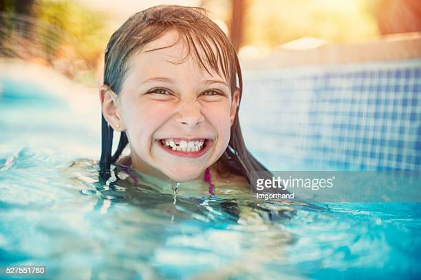 Happy little girl laughing in swimming pool