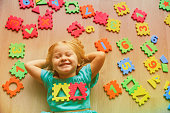 happy cute little girl learn numbers and shapes, play with puzzle