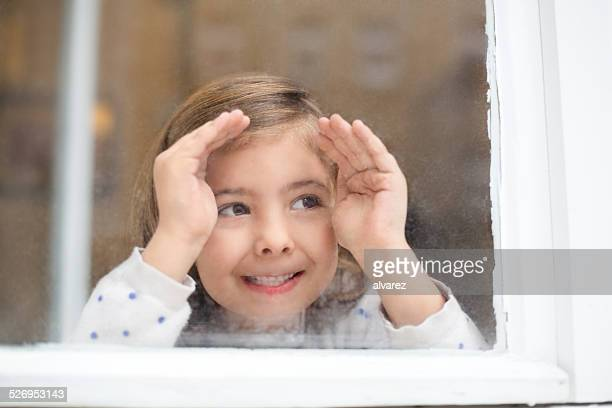 Happy little girl looking outside window