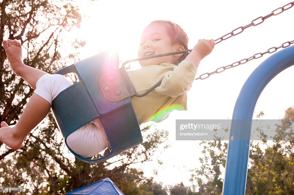 Happy little girl on swing at playground : Stock Photo