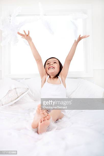 Bambina felice giocare con piume nel letto
