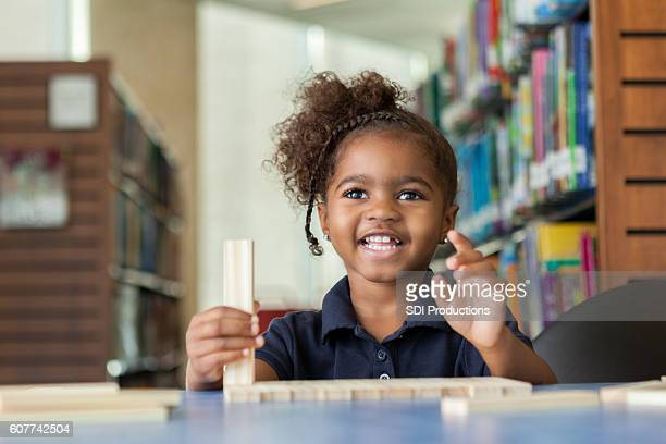 Happy little girl playing with learning blocks at the library