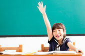 happy little girl  raised hands in classroom