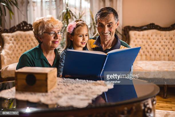 Happy little girl reading a book with her grandparents.