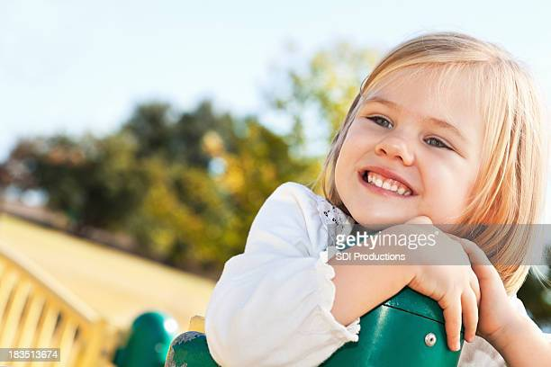 Happy Little Girl Resting at a Playground