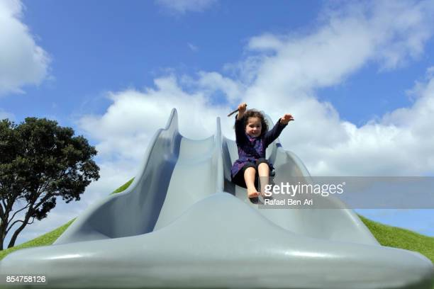 Happy little girl sliding on a big slide in the playground