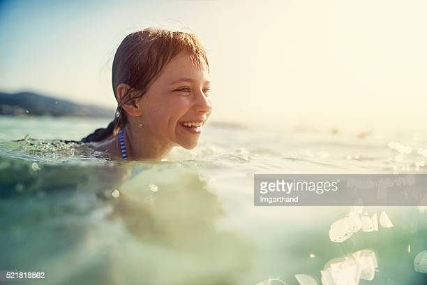 Happy little girl swimming in mediterranean sea