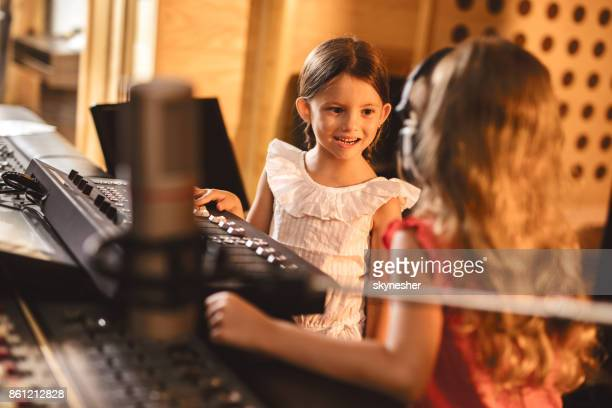 Happy little girl talking to small commentator in radio station.