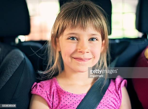 Happy little girl travelling in car