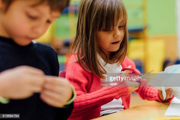 Happy Little Girl using scissors in kindergarten.