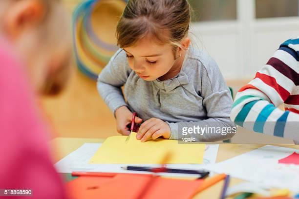 Glückliches kleines Mädchen mit Schere in bereits im Kindergarten.