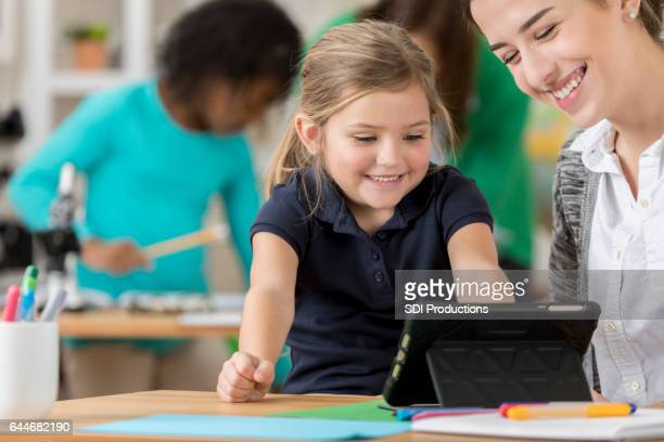 Happy little girl watches something on digital tablet in class
