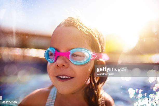 Happy little girl wearing swimming goggles in a pool