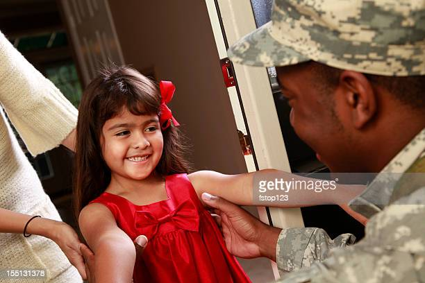 Happy little girl welcoming home military soldier father.