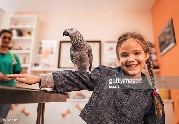 Fillette heureuse avec un perroquet gris sur ses bras.