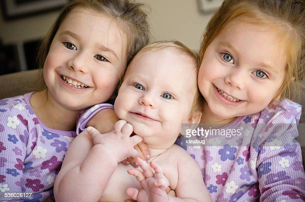 Happy Little Girls Cuddling with Their Baby Sister