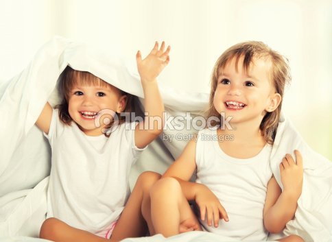 happy little girls twins sister in bed under the blanket : Stock Photo