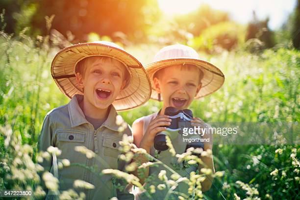 Happy little safari boys exploring widerness