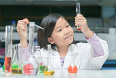 Happy little scientist in lab coat making experiment with test tube in chemical laboratory, science and education concept