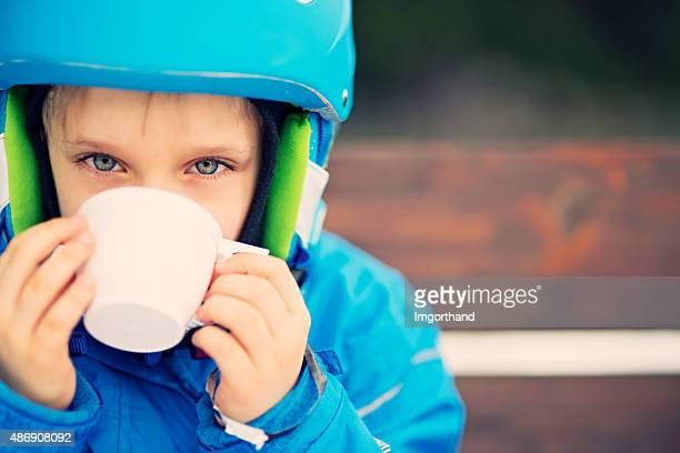 Happy little skier drinking hot tea