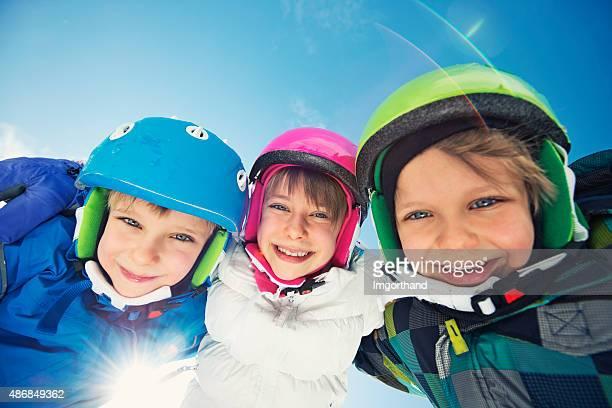 Happy little skier kids in winter