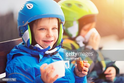 Happy little skiers resting, drinking tea and eating cookies
