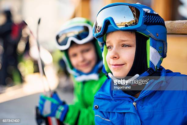 Happy little skiers waiting outside of ski rent service building