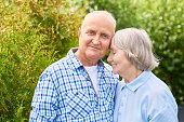 Portrait of loving senior couple embracing tenderly posing for camera in beautiful garden