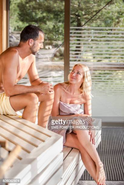 happy love couple sitting inside a hot panorama sauna wearing a towel only while enjoying the heat and detoxing and sweating
