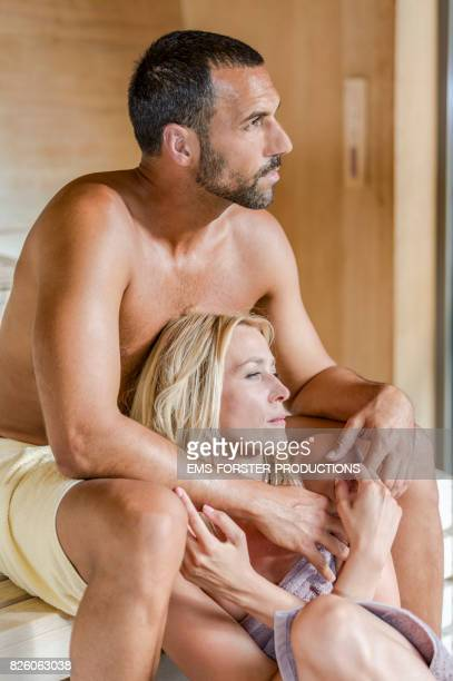 happy love couple sitting very close together and caress inside a outdoor sauna while enjoying the heat and harmony and detoxing and sweating