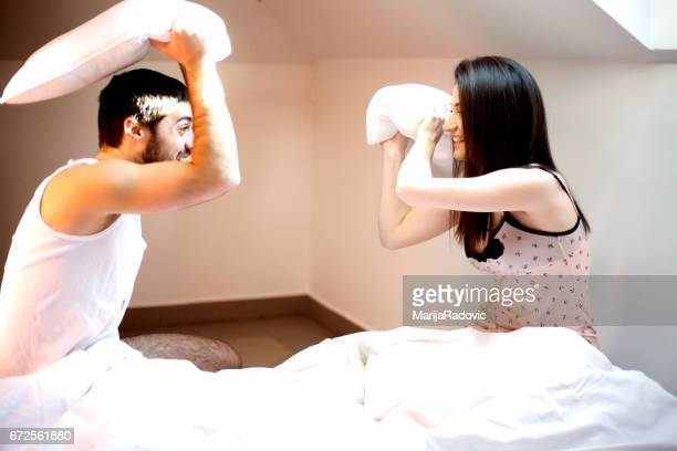 Happy loving couple having a pillow fight in bed