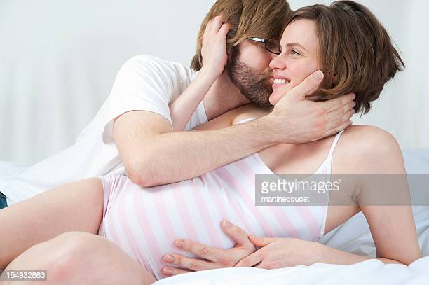 Happy loving expecting couple in embrace on bed.