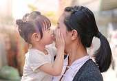 Happy loving family, mother and child girl kissing.