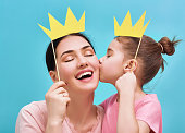 Funny family on a background of bright blue wall. Mother and her daughter girl with a paper accessories. Mom and child are holding paper crown on stick.