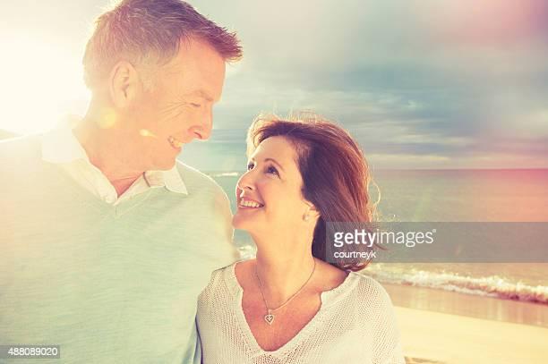 Happy loving mature couple on the beach.