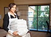 Happy maid with a stack of towels
