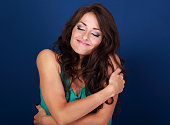 Happy makeup woman hugging herself with natural emotional enjoying face. Love concept of yourself body and face on blue background