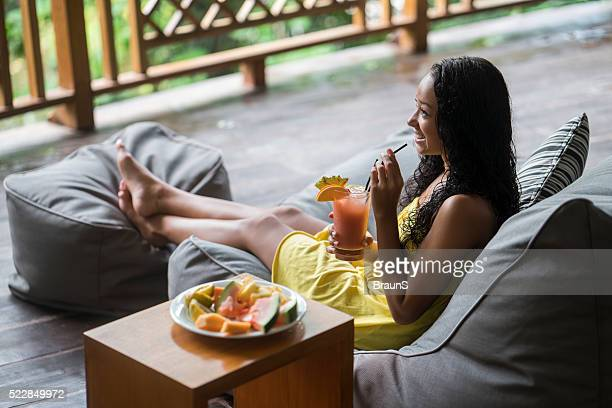 Happy Malaysian woman enjoying in fruit cocktail on a balcony.