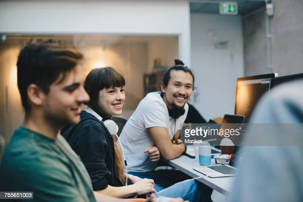 Happy male and female computer programmers talking at desk in office