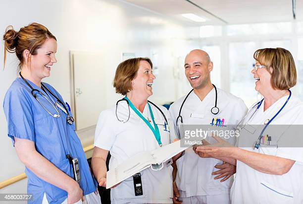 Happy male and female doctors laughing in hospital