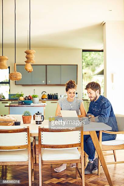 Happy male and female hipsters using laptop at dining table