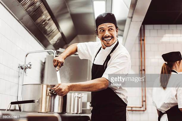 Happy male chef looking away while preparing food in kitchen