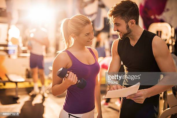 Happy male coach and young woman planning a training together.