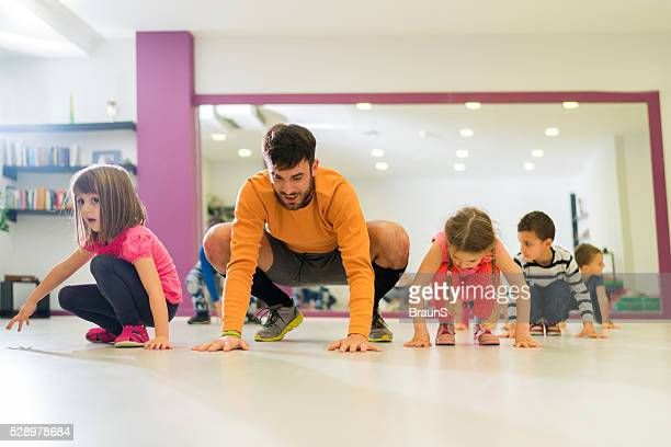 Happy male coach exercising with group of children.